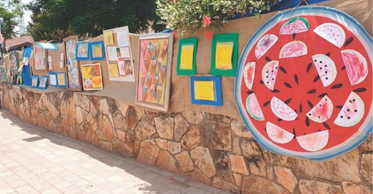 התערוכה מחוץ לגן. עוברי אורח נהנים מהצבעוניות